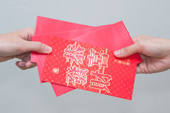 Att ge sig för kvinnahand som är rött, packar att innehålla pengar in Arkivfoton