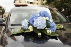 Att gifta sig blommar på en dyr bil Arkivbilder