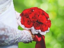 Att gifta sig den eleganta buketten av den röda rosen blommar i handbrud Royaltyfri Bild