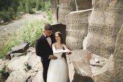 Att gifta sig förälskat kyssa för par och att krama nära vaggar på härligt landskap Arkivbilder