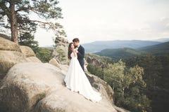 Att gifta sig förälskat kyssa för par och att krama nära vaggar på härligt landskap Arkivfoton