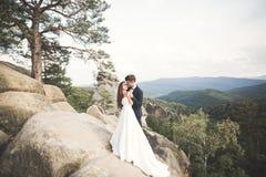 Att gifta sig förälskat kyssa för par och att krama nära vaggar på härligt landskap Royaltyfri Bild
