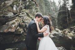 Att gifta sig förälskat kyssa för par och att krama nära vaggar på härligt landskap Arkivbild