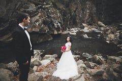Att gifta sig förälskat kyssa för par och att krama nära vaggar på härligt landskap Royaltyfri Foto