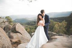 Att gifta sig förälskat kyssa för par och att krama nära vaggar på härligt landskap Royaltyfria Foton