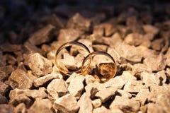 Att gifta sig guld- cirklar på vaggar Arkivbild