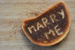 Att gifta sig mig skrapade på till en skiva av bränt vitt rostat bröd arkivfoto