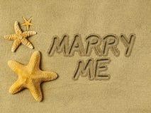 Att gifta sig mig text på sand Arkivbild
