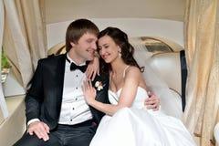Att gifta sig par är att krama i en bil Royaltyfria Foton