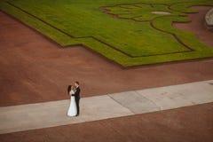 Att gifta sig par är stående och kyssa i gatorna av den gamla staden Fotografering för Bildbyråer