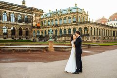 Att gifta sig par är stående och kyssa i gatorna av den gamla staden Arkivbild