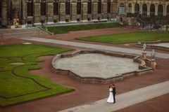 Att gifta sig par är stående och kyssa i gatorna av den gamla staden Royaltyfri Foto