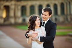 Att gifta sig par är stående och kyssa i gatorna av den gamla staden Arkivfoton