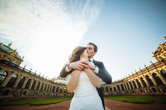 Att gifta sig par är stående och kyssa i gatorna av den gamla staden Royaltyfri Bild