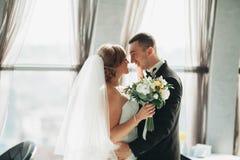 Att gifta sig par är stående och kyssa i hotell Arkivfoton