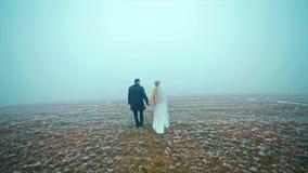 Att gifta sig par går vintern på Snowed surret för fältet stock video