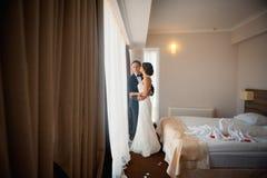 Att gifta sig par inomhus är att krama sig Arkivbild