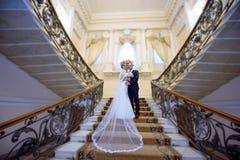 Att gifta sig par inomhus är att krama sig Arkivfoto