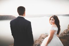 Att gifta sig par som kysser och kramar på, vaggar nära det blåa havet Royaltyfria Foton