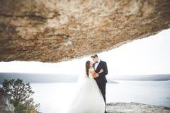 Att gifta sig par som kysser och kramar på, vaggar nära det blåa havet Royaltyfri Foto