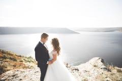Att gifta sig par som kysser och kramar på, vaggar nära det blåa havet Royaltyfri Fotografi