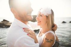 Att gifta sig par som kysser och kramar på, vaggar nära det blåa havet Fotografering för Bildbyråer