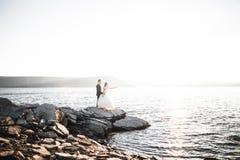 Att gifta sig par som kysser och kramar på, vaggar nära det blåa havet Arkivfoton