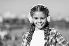 Att gilla vad du g?r, ?r lycka Lycklig barnkl?derh?rlurar Lycklig liten flicka Den lilla flickan lyssnar till utomhus- musik arkivfoton