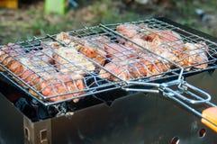 Att grilla på ett varmt gallergaller med brand och rök på sidan fyllde med nötkött och griskött och svinet Fotografering för Bildbyråer