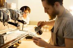 Att hälla för bartender mjölkar in i kaffe arkivfoto
