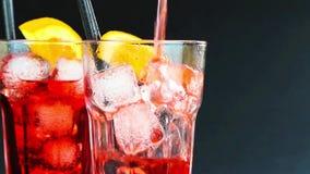 Att hälla för bartender som är rött, spritz aperitifaperolcoctailen med två orange skivor och iskuber på svart stock video