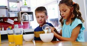 Att hälla för flicka mjölkar in i den sädes- bunken i kök stock video