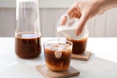 Att hälla för kvinna mjölkar in i exponeringsglas med kallt brygdkaffe royaltyfria foton