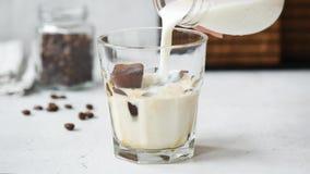 Att hälla för ultrarapid mjölkar in i exponeringsglas med kuber för iskaffe arkivfilmer