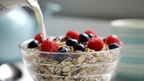 Att hälla mjölkar från tillbringaren på bunken av sund frukostmysli arkivfilmer
