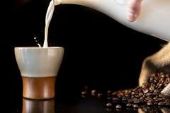 Att hälla mjölkar i en härlig kopp kaffe med en färgstänk av mjölkar arkivbilder