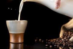 Att hälla mjölkar i en härlig kopp kaffe med en färgstänk av mjölkar royaltyfri bild