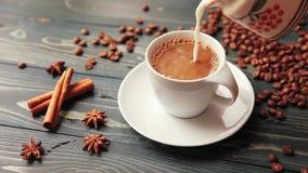 Att hälla mjölkar in i en hemlagad kaffekopp Kaffebönor, kanelbruna pinnar och en smula på en trätabell lager videofilmer