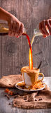 Att hälla mjölkar in i en kopp kaffe Fotografering för Bildbyråer
