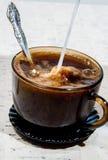 Att hälla mjölkar in i en kupa av kaffe. Royaltyfri Fotografi