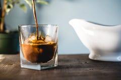 Att hälla mjölkar och kaffe i ett exponeringsglas royaltyfri bild