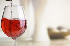 Att hälla steg vin in i ett vinexponeringsglas royaltyfria bilder
