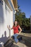 att huka sig ned parkera bilen i garage henne bredvid vertikal kvinna Arkivbilder