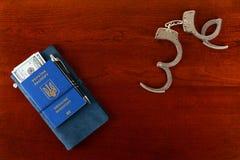Att inte vara ett hem för korrumperat folk Ukrainskt biometric pass och handbojor på tabellen Royaltyfria Foton