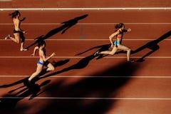 att köra för tre kvinnalöpareskuggor sprintar loppet Royaltyfri Bild
