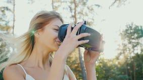 Att att kasta sig in i virtuell verklighet En ung kvinna sätter på en hjälm av en virtuell verklighet i solen Vinden knackar henn arkivbild