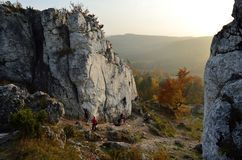 Att klättra på Jurassic vaggar under solnedgång på en bakgrund av den guld- hösten fotografering för bildbyråer