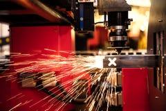 Att klippa av arkmetallgnistor flyger från laser vid automatisk klippCNC royaltyfri fotografi