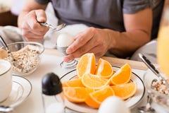 Att knäcka för man öppnar ett kokt ägg för frukost Arkivfoton