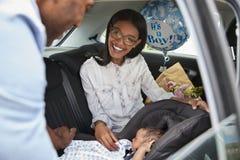 Att komma med för föräldrar som är nyfött, behandla som ett barn hem i bil royaltyfri fotografi